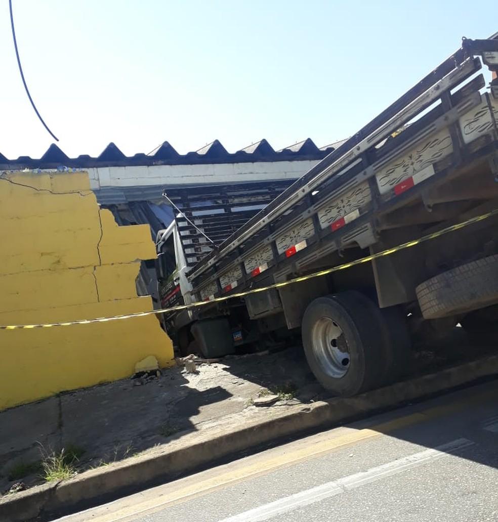 #PraCegoVer: Caminhão invade propriedade - guincho reboca o caminhão