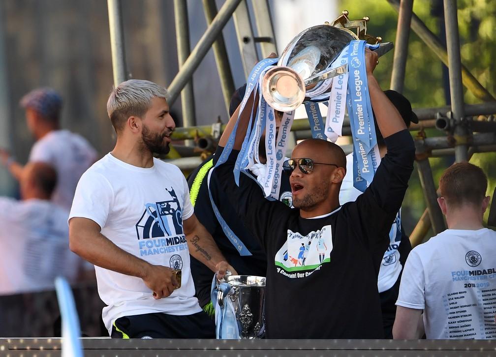 Kompany ergue o troféu da Premier League em desfile ao lado de Agüero — Foto: AFP