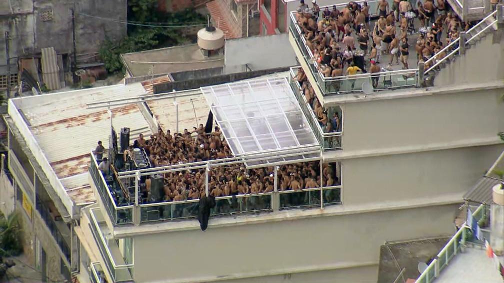 Festa reúne centenas de pessoas no alto do Vidigal, na manhã desta quarta (17); na laje de baixo, um DJ toca para a multidão — Foto: Reprodução/TV Globo