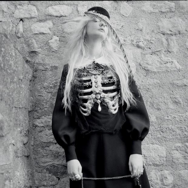 Vestido de lã e seda com bordados de cristais e pérolas, colar e acessório de cabeça com penas. (Foto: Gia Coppola)