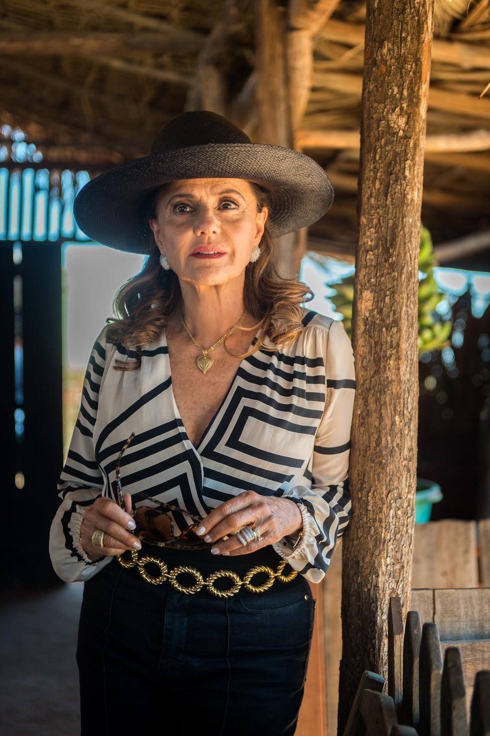 O visual de Sophia inclui ainda chapéus no estilo Panamá, que agregam dupla funcionalidade: proteção contra sol e um charme a mais. Além de sua marca registrada: o colar dourado com pingente de coração (Foto: TV Globo/Raquel Cunha)