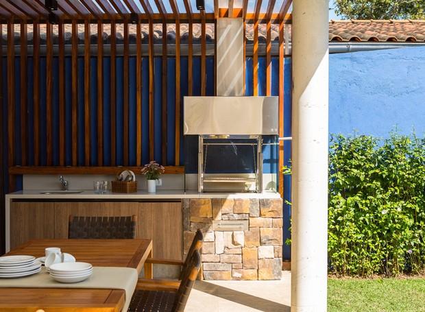 Espaço gourmet da casa de praia que é projeto dos arquitetos, Pérsio Mendes e FM Arquitetura. A churrasqueira fica sob pergolado de madeira, que desce atrás dela em forma de painel (Foto: Edu Castello / Editora Globo)