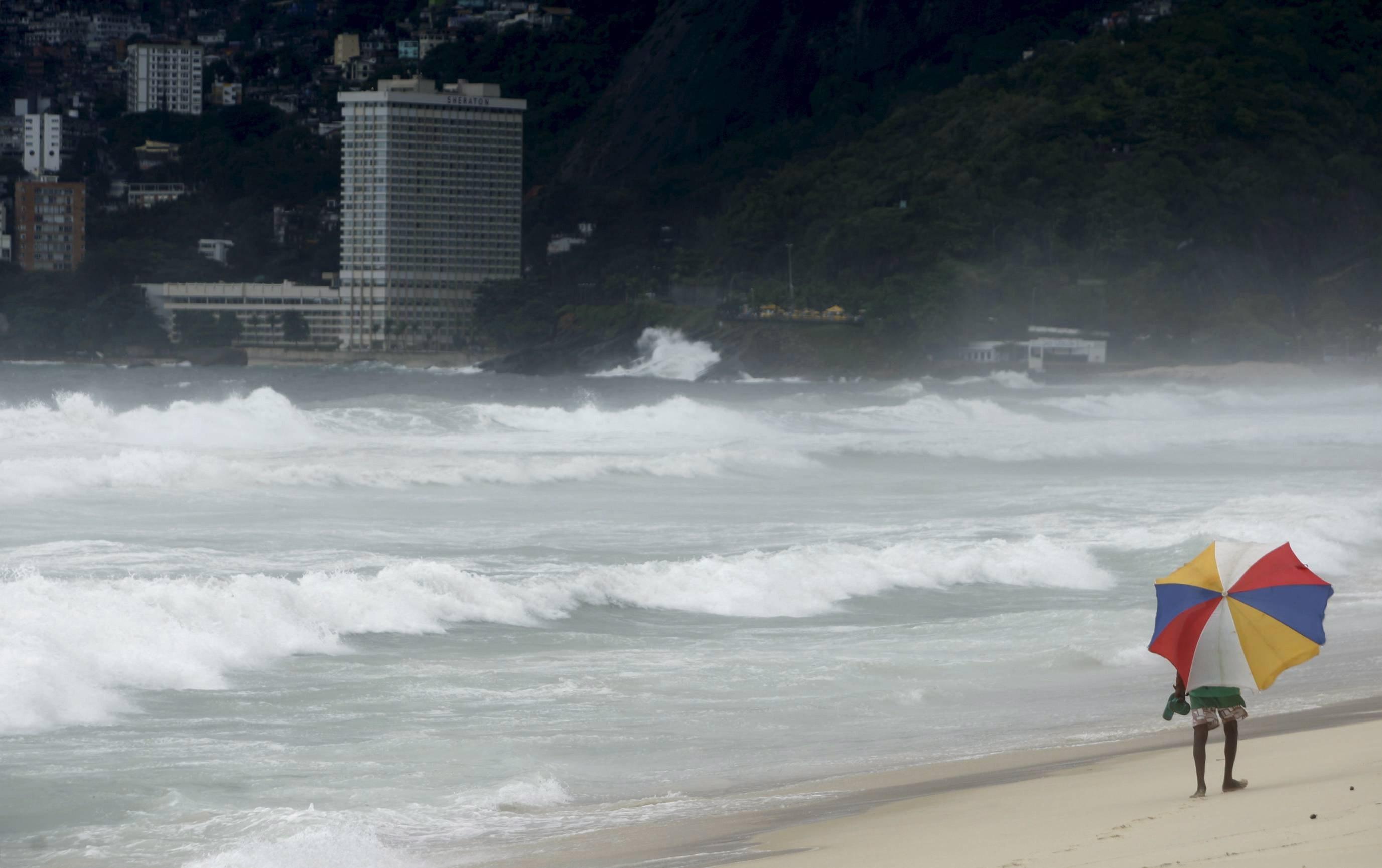 Homem caminha na Praia de Ipanema