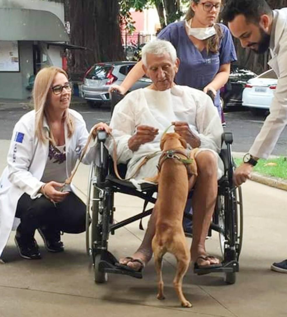 """A psicóloga Noemi Peres Honorato (à esq.) explica que visita dos pets garante benefícios clínicos aos pacientes: """"Ameniza o sofrimento"""" — Foto: HC Famema/Divulgação"""