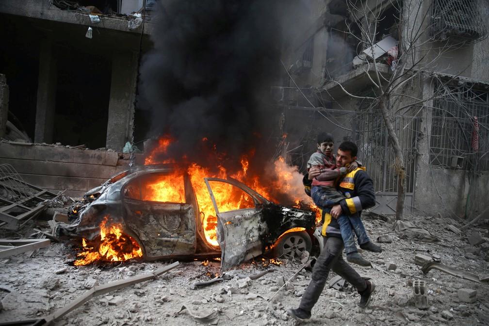 6 de janeiro - Um membro da Defesa Civil carrega uma criança ferida, em Damasco, na Síria (Foto: Bassam Khabieh/Reuters)