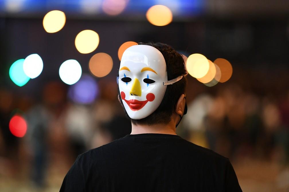 Homem com máscara atrás da cabeça participa de protestos no distrito comercial central de Hong Kong nesta sexta-feira (4). — Foto: Mohd Rasfan/AFP