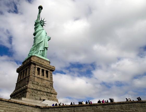 Turistas visitam a Estátua da Liberdade. O monumento foi reaberto ao público após o Estado de Nova York concordar em pagar os custos do local enquanto parte dos serviços do governo federal está paralisada sem o acordo para aprovar o orçamento dos EUA (Foto: John Minchillo/AP)