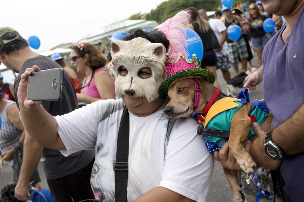 Mulher tira selfie com cachorro fantasiado em bloco para animais no Rio (Foto: Silvia Izquierdo/AP)