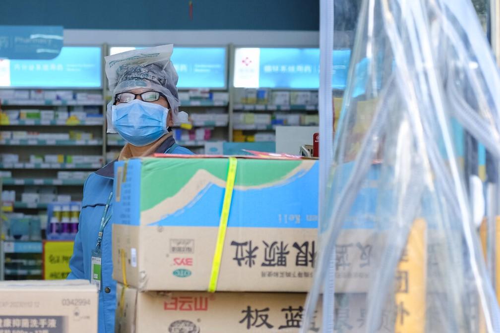 Funcionário de uma farmácia em Wuhan veste uma máscara de proteção e cobre a cabeça com uma sacola plástica para se proteger contra a epidemia de coronavírus — Foto: Arek Rataj/AP/Arquivo
