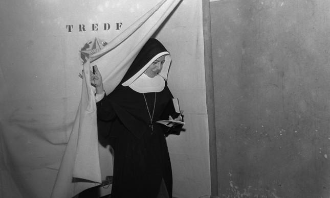 Freira deixa cabine de votação com cédula na mão durante as eleições de 1958