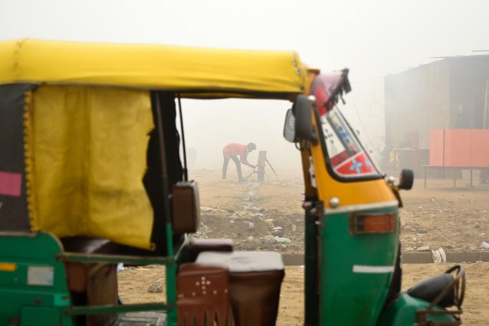 Um jovem lava as mãos usando a água de uma bomba manual ao lado de um riquixá estacionado em Greater Noida, perto de Nova Delhi, na Índia. Durante o inverno, uma névoa espessa envolve a maior parte do norte do país, causada pela poeira, queima de plantações, emissões das fábricas e pela queima de carvão e pilhas de lixo  — Foto:  R S Iyer/AP