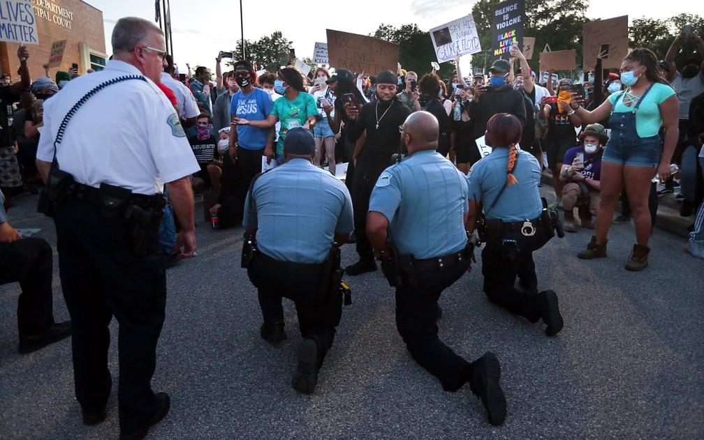 Policiais se ajoelham diante de manifestantes em Ferguson, no Missouri; gesto é um dos símbolos dos protestos antirracistas nos EUA — Foto: Robert Cohen/St. Louis Post-Dispatch via AP