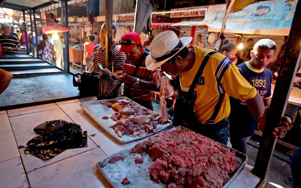 Consumidores examinam carne estragada, misturada à carne fresca, oferecida em Mercado em Maracaibo, na Venezuela, no dia 19 de agosto (Foto: AP Photo/Fernando Llano)