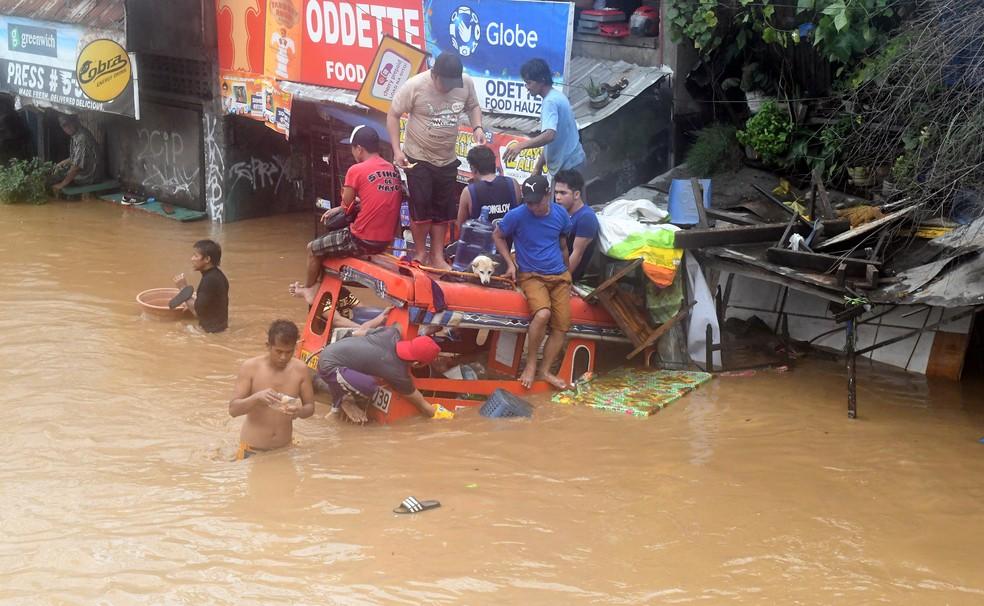 Moradores no topo de um veículo parcialmente submerso em uma estrada inundada na cidade de Cagayan de Oro, nas Filipinas (Foto: REUTERS / Froilan Gallardo)