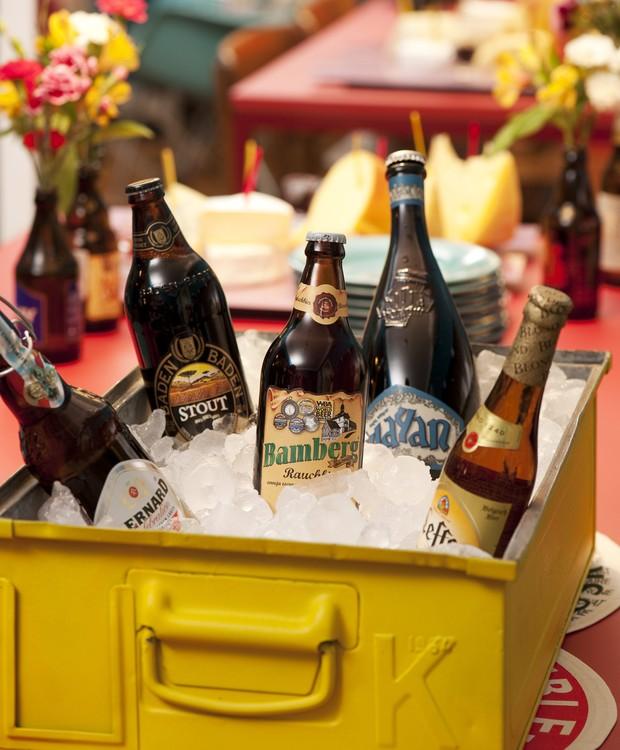 Garrafas de cervejas importadas dentro de uma gaveta amarela de metal com gelo (Foto: Iara Venanzi / Editora Globo)