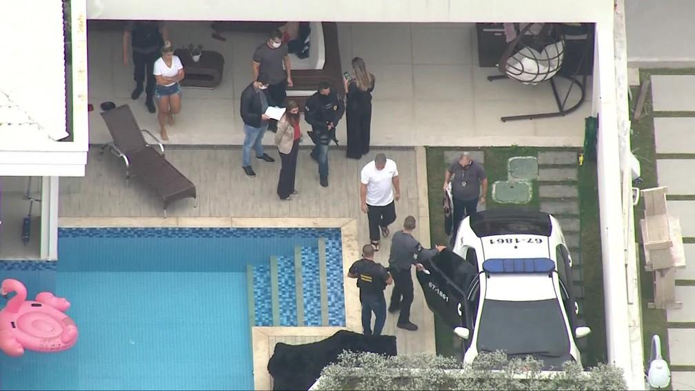 Suel (de camisa branca e chinelos) é conduzido para um carro da polícia ao ser preso em casa, no Recreio — Foto: Reprodução/TV Globo