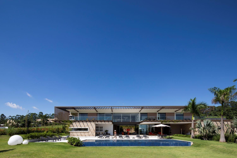 FACHADA   A vegetação abraça o entorno da casa, deixando-a totalmente integrada com a natureza. Nela foram inseridas palmeiras para valorizar arquitetura e paisagismo (Foto: Maira Acayaba / Divulgação)