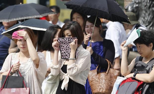 Moradores enfrentam calor na tarde desta sexta-feira (12) em Tóquio, capital do Japão (Foto: AP)