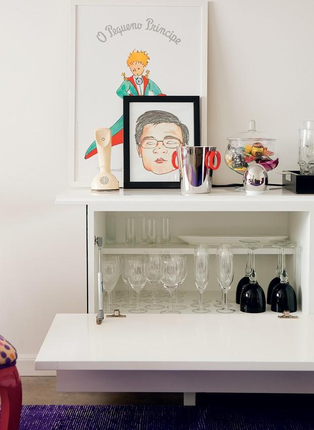 """Dentro do móvel desenhado pelos arquitetos Tatiana Yokota e Kleber Alves, a prateleira recuada aproveita melhor o espaço. """"A altura de 15 cm é suficiente para as taças menores. Na frente, com 35 cm, ficam as maiores"""", diz Tatiana. O acabamento é de laca, da (Foto: Edu Castello)"""