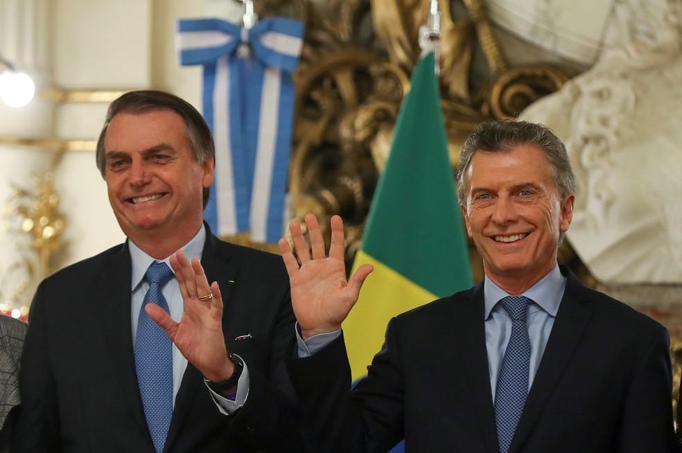 Jair Bolsonaro e Mauricio Macri acenam em salão da Casa Rosada, em Buenos Aires — Foto: Agustin Marcarian/Reuters