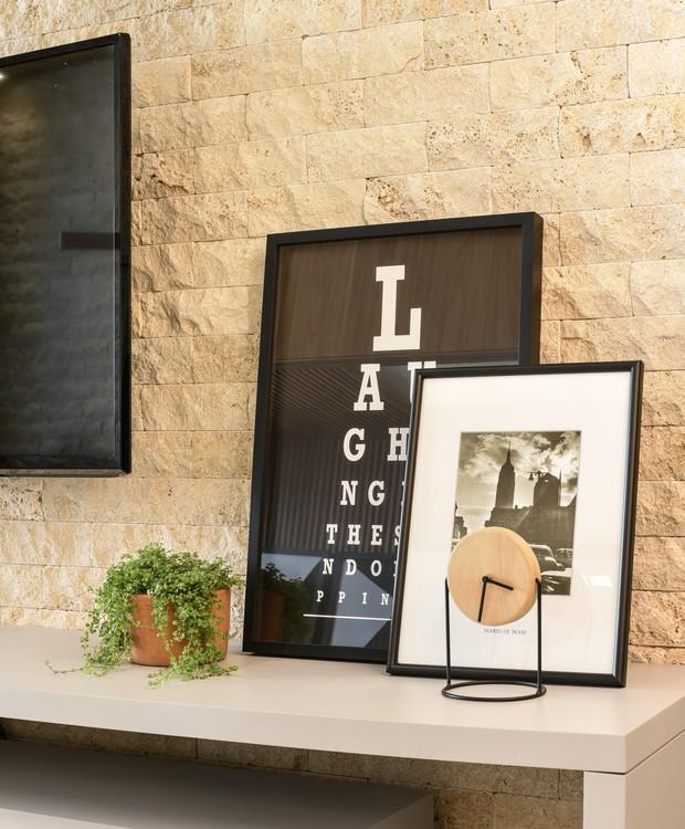 No detalhe, fica mais fácil visualizar os tijolinhos feitos com travertino, que cobre trechos da sala de estar (Foto: Laura Sá/Divulgação)