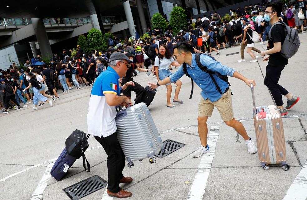 Passageiros e manifestantes fogem da polícia durante protesto no aeroporto internacional de Hong Kong, na manhã deste domingo (1º) — Foto: REUTERS/Kai Pfaffenbach