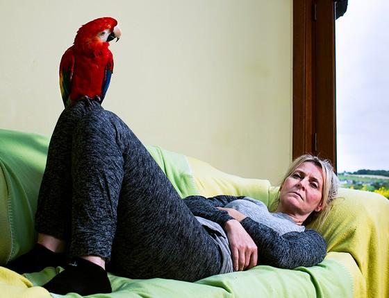 Karen Adams e arara Scarlet. Ela e seu marido cuidam de outras duas araras e de 17 papagaios (Foto: Miisha Nash)