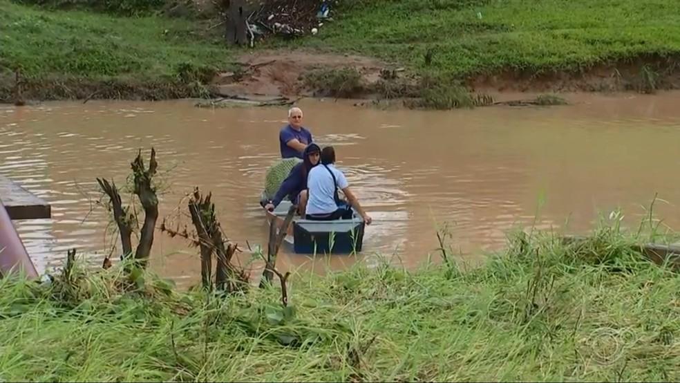 Morador está ajudando a fazer a travessia de ribeirão com barco após ponte de bairro ser levada durante temporal em Laranjal Paulista — Foto: TV TEM/Reprodução