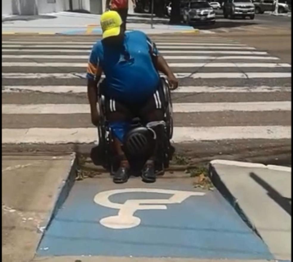 Cadeirante tem dificuldade em passar para calçada da Praça da Bandeira (Foto: Reprodução)