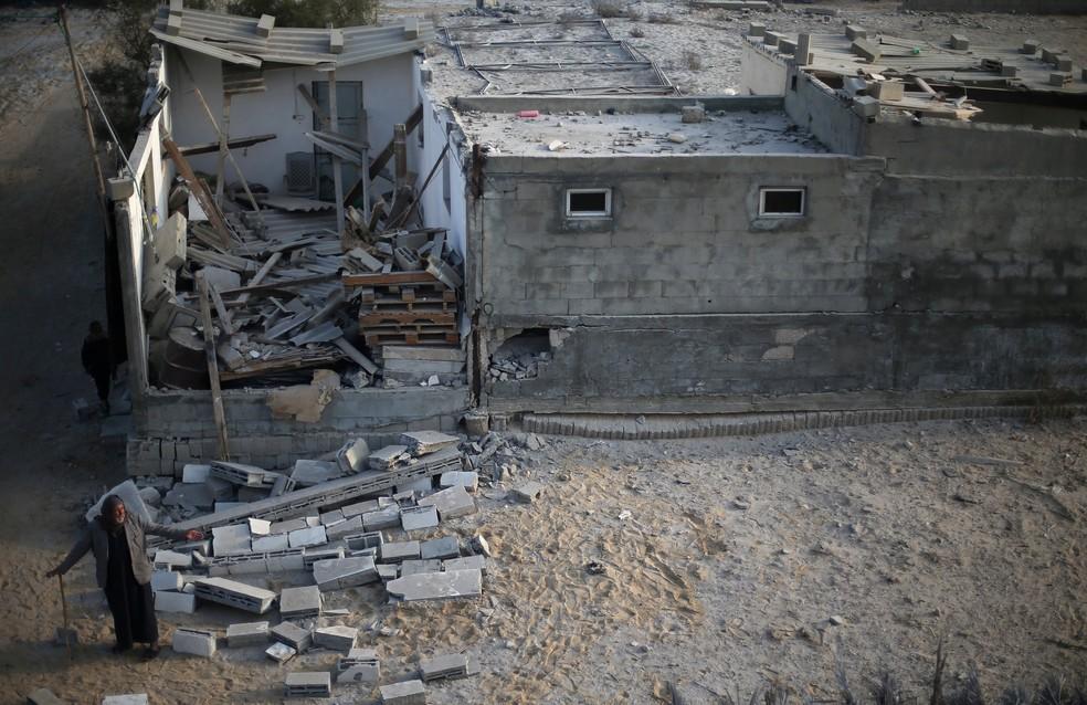 Palestino em frente à casa atingida por bombardeiro israelense próximo a um território do Hamas na quarta-feira (13) (Foto: Ibraheem Abu Mustafa/ Reuters)