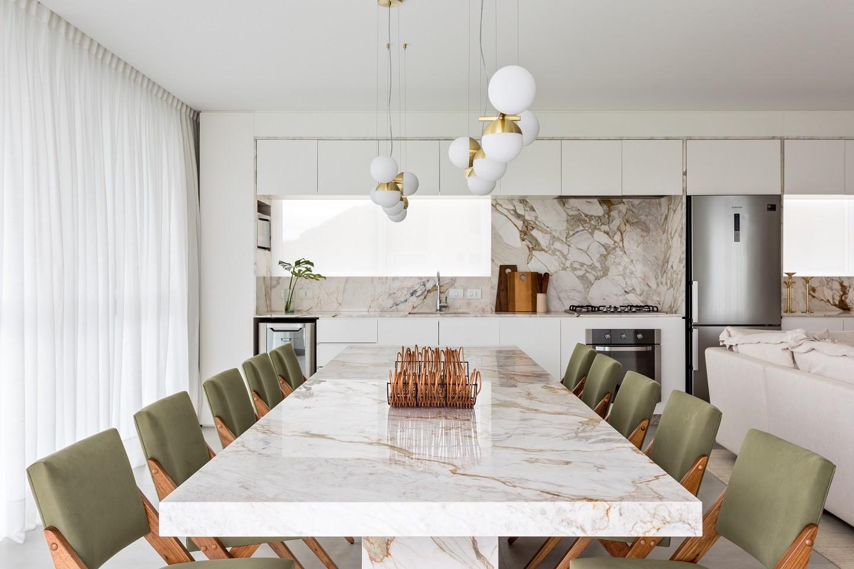 Cozinha com bancada de mármore, cadeiras verde e acessórios de cozinha.