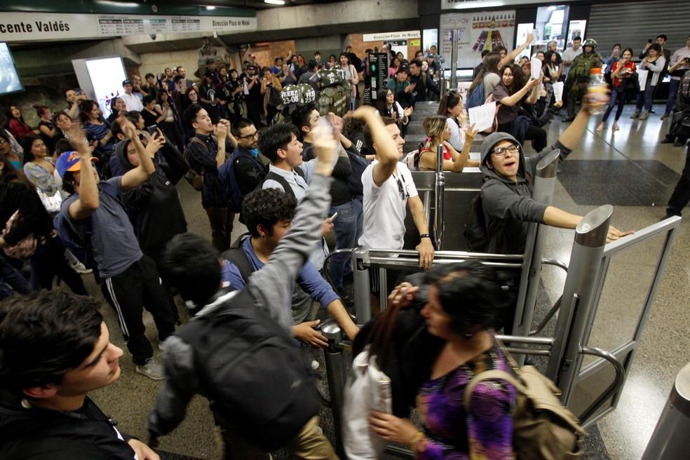 Manifestantes pulam catraca em estação de metrô durante protesto contra aumento da tarifa de transporte pública em Santiago, no Chile, na sexta-feira (18) — Foto: Reuters/Carlos Vera