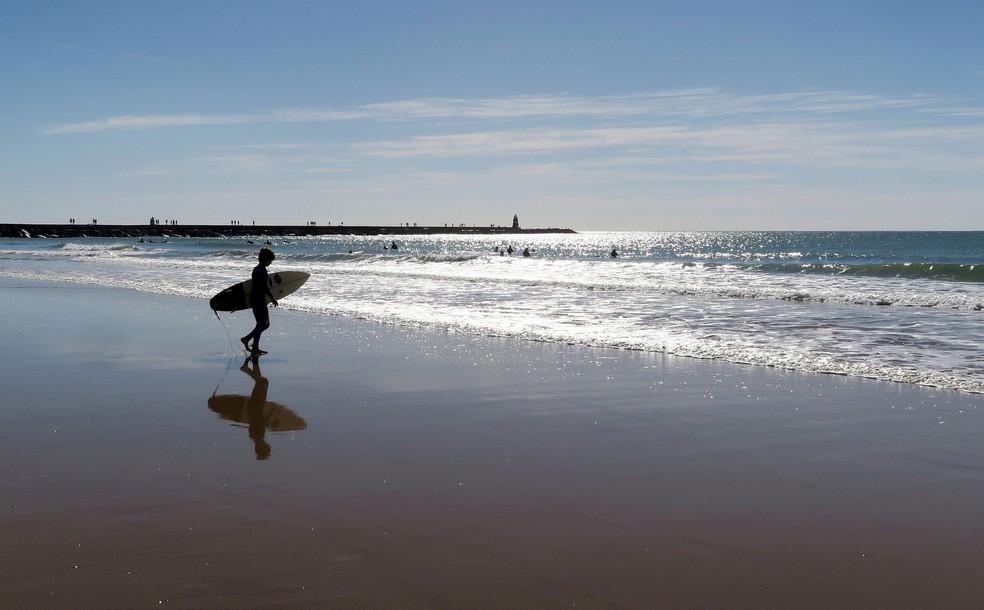 -  Surfista caminha na praia da Rocha, em Portimão  Portugal , em imagem de arquivo de 6 de novembro de 2016  Foto: John Schults/ Reuters