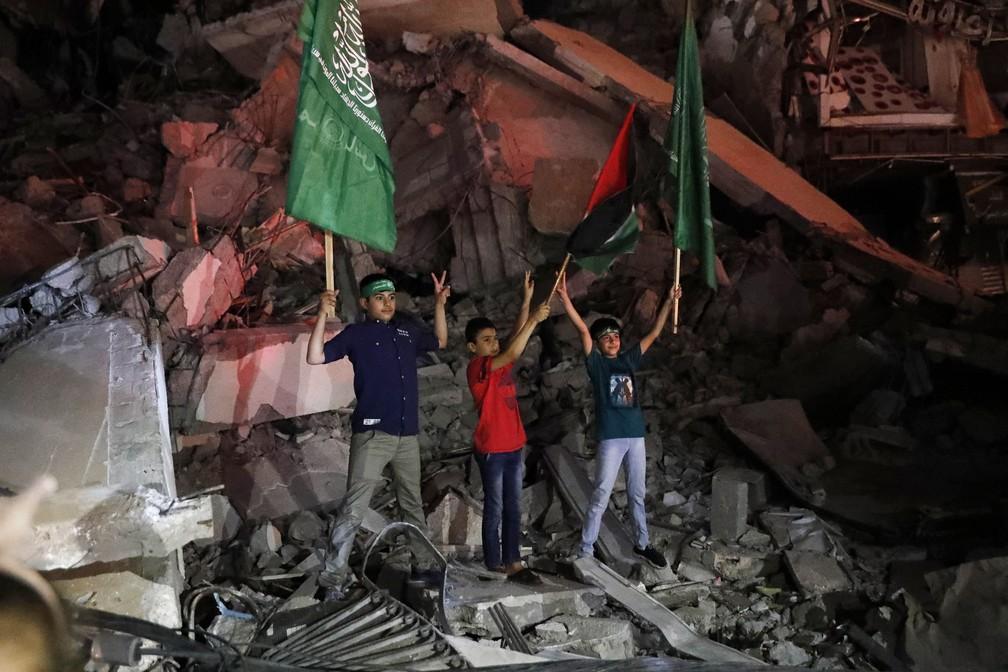 Crianças palestinas celebram o acordo de cessar-fogo entre Israel e o Hamas na Cidade de Gaza, no início da sexta-feira (21) — Foto: Adel Hana/AP