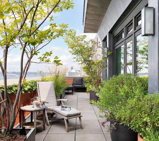 Espreguiçadeiras, sofás e plantas criam área de descanso na varanda (Foto: Douglas Elliman/ Reprodução)