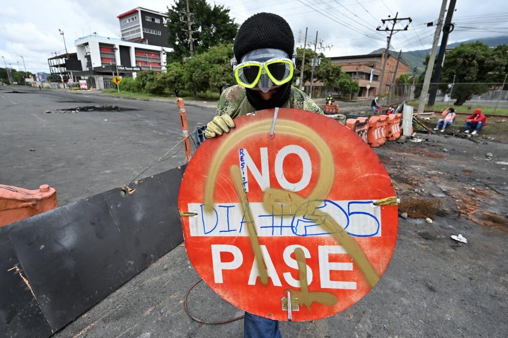 Homem segura placa em barricada montada em Cali, na Colômbia, nesta segunda-feira (3), novo dia de protestos — Foto: Luis Robayo/AFP