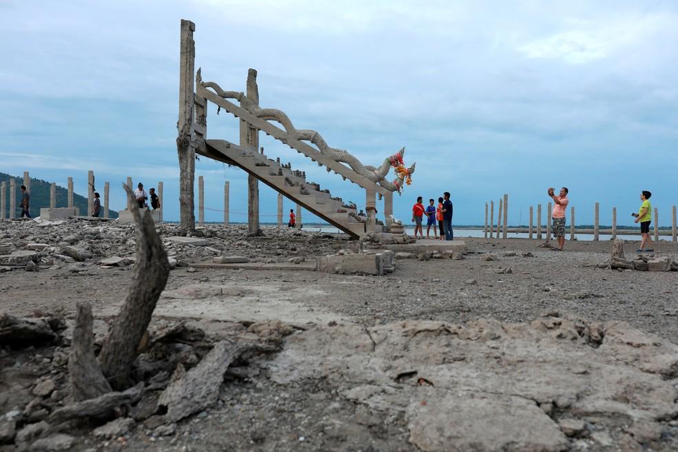 Pessoas visitam ruínas de um templo budista que ressurgiu em uma represa seca devido à seca em Lopburi, na Tailândia — Foto: Soe Zeya Tun/ Reuters