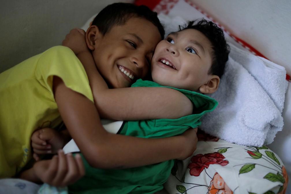 Daniel Vieira, que tem dois anos e nasceu com microcefalia, é abraçado pelo irmão na casa em que moram em Olinda — Foto: Ueslei Marcelino/Reuters
