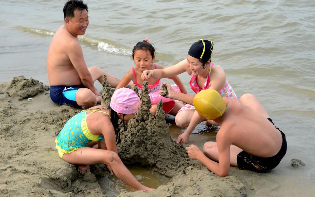 Uma família constrói castelos de areia na praia no Songdowon International Children's Camp, na cidade de Wonsan, na Coreia do Norte, em foto não datada divulgada pela agência KCNA (Foto: KCNA/via Reuters )