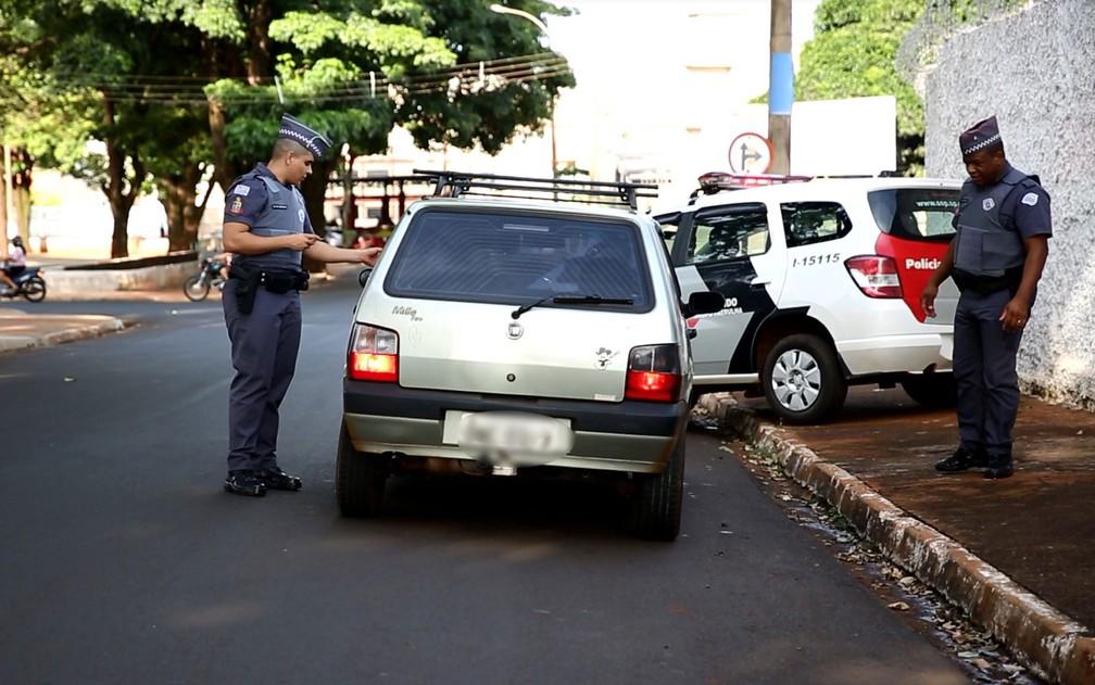 Soldado Henrique (à esquerda) e sargento Louzada (à direita) durante blitz em carros em Ituverava — Foto: Marcelo Brandt/G1