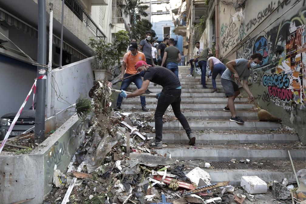 5 de agosto - Pessoas fazem limpeza após explosão em Beirute, no Líbano — Foto: Hassan Ammar/AP