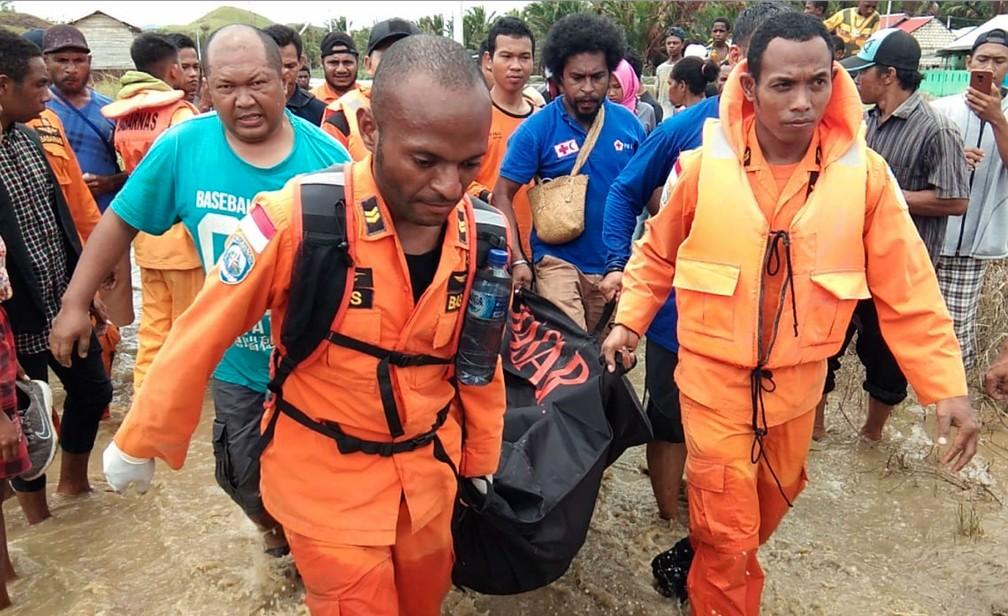 Policiais e socorristas retiram corpo de vítima da enchente em Sentani, na província de Papua, na Indonésia  — Foto: Basarnas via AP