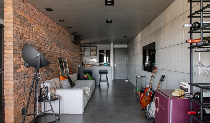 Paredes de tijolinhos e concreto dão toque industrial ao apê de 81 m²
