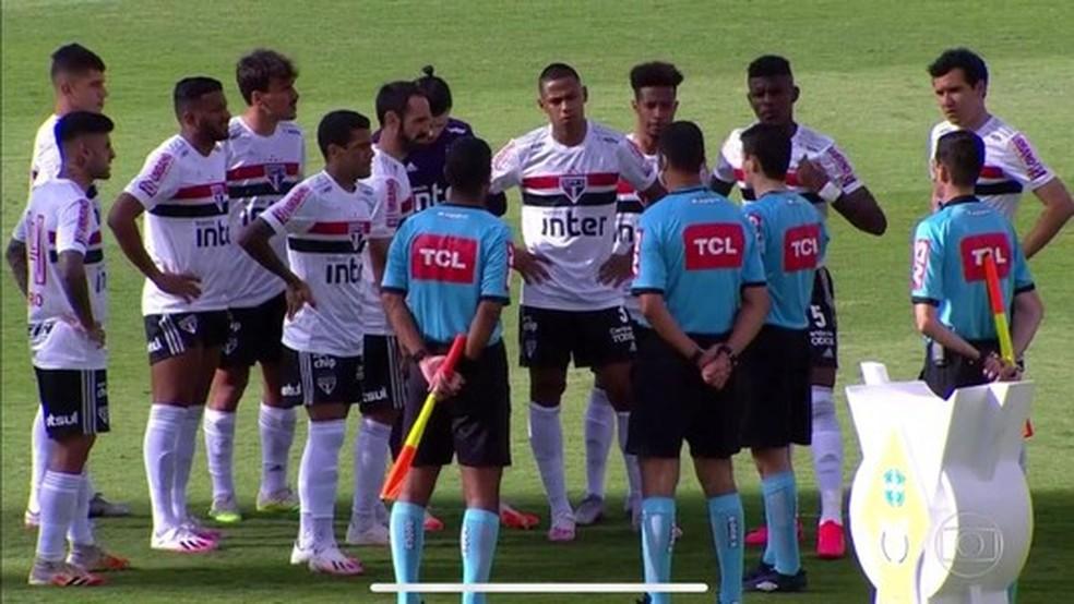 Jogadores do São Paulo conversam com a arbitragem antes do adiamento do jogo ser confirmado, em Goiânia — Foto: Reprodução/TV Globo