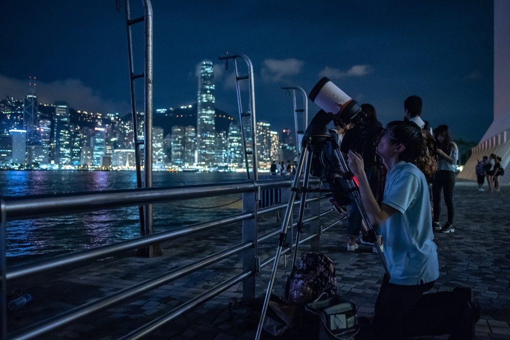Grupo se posiciona para assistir eclipse lunar total em Hong Kong (Foto: Philip Fong/AFP )