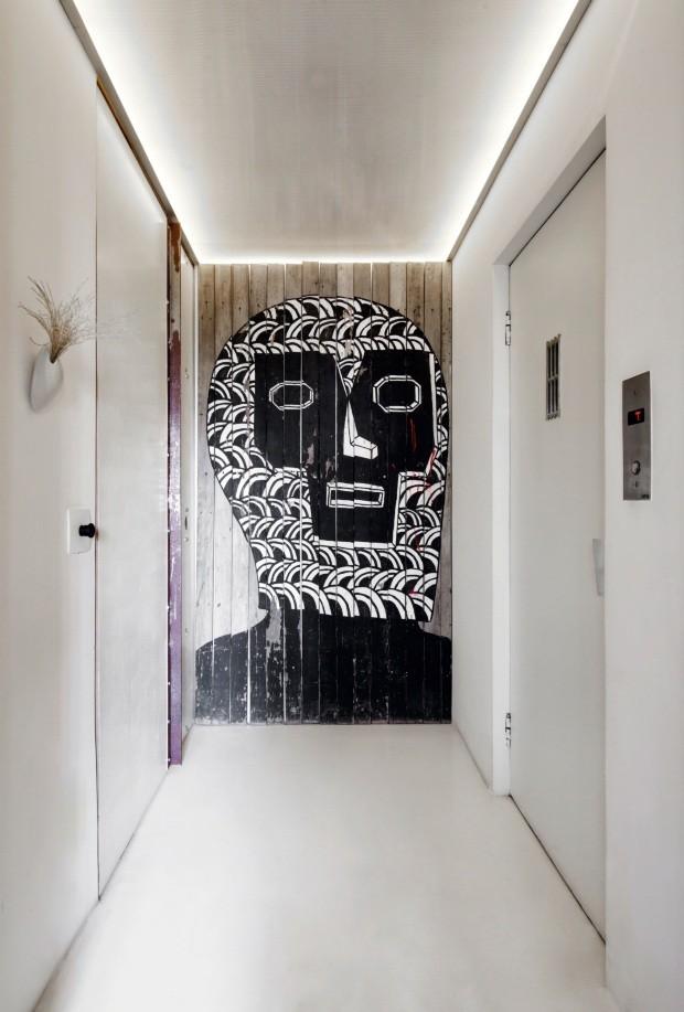 O painel de grafite, aproveitado de tapumes da obra de um prédio em São Paulo, contrasta com o branco das paredes e do piso com acabamento de epóxi. O teto é rebaixado com forro de policarbonato alveolar e luz de LED instalada no perímetro (Foto: Maíra Acayaba / Editora Globo)