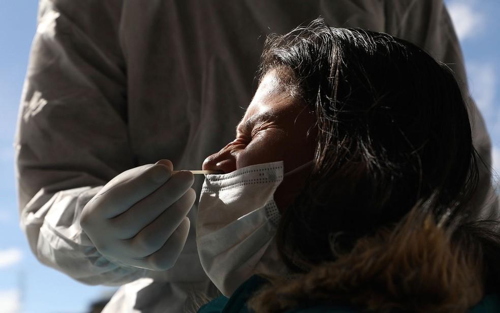Mulher é submetida a coleta de material para teste de Covid-19 em Bogotá, na Colômbia, na quarta-feira (27) — Foto: Fernando Vergara/AP