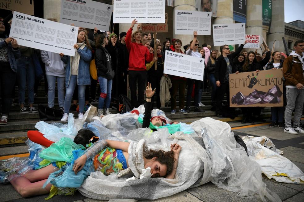 Greve pelo clima: Na Polônia, ativistas fizeram uma performance enrolados em plásticos para criticar o consumo. A manifestação foi na Varsóvia, nesta sexta (20). — Foto: Maciek Jazwiecki/Agencja Gazeta via Reuters