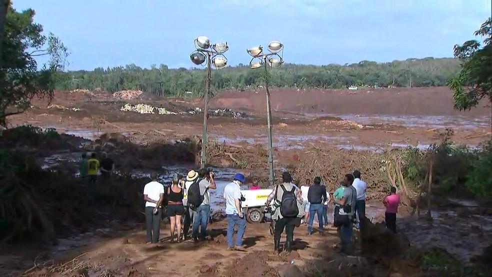 Pessoas observam área destruída pela lama de barragem da Vale que se rompeu em Brumadinho (MG) — Foto: Reprodução/TV Globo