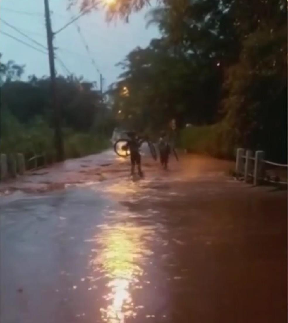 Moradores levaram bicicletas para passar por córrego que transbordou em Jundiaí — Foto: Reprodução/TV TEM